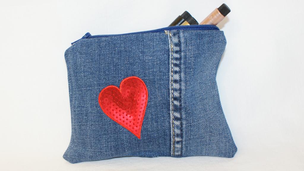 Kleiner Beutel aus Jeansstoff mit blauem Reißverschluss, rotem Herz auf der Vorderseite und silbernen Glitzerherzchen auf der Rückseite.