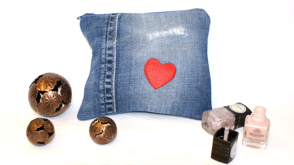 Jeanstäschchen ich aus einer blauen Jeans mit destroyed Effekten mit rotem Herz darauf und blau-weiß-rot kariertem  Innenfutter.