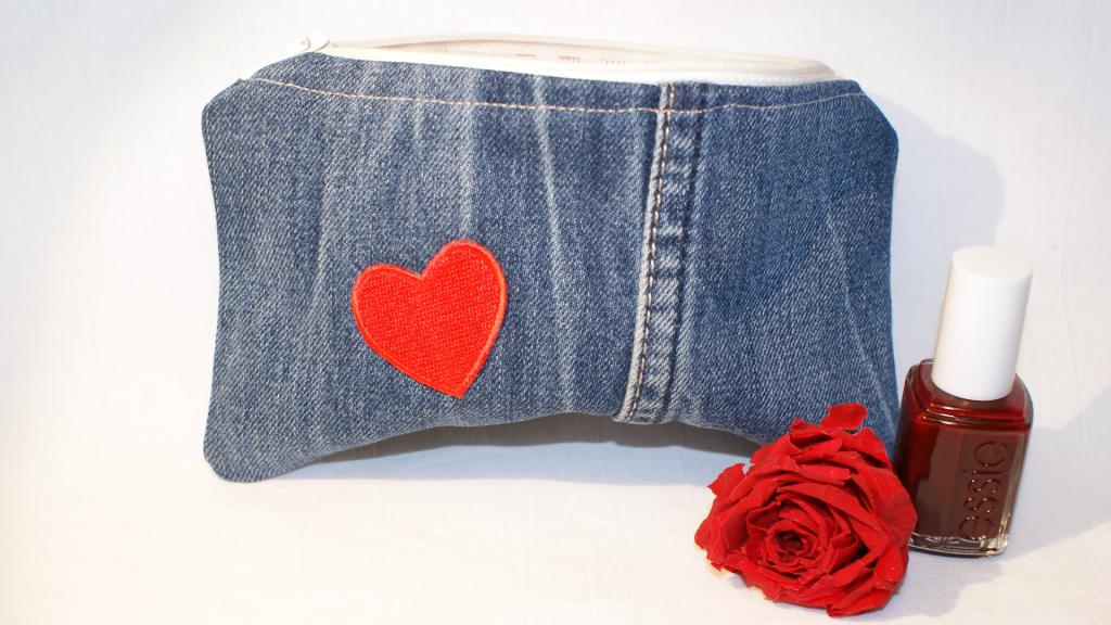 Jeansbeutel aus blauem Jeansstoff mit weißem Reißverschluss und die Vorderseite ziert ein rotes Herz .
