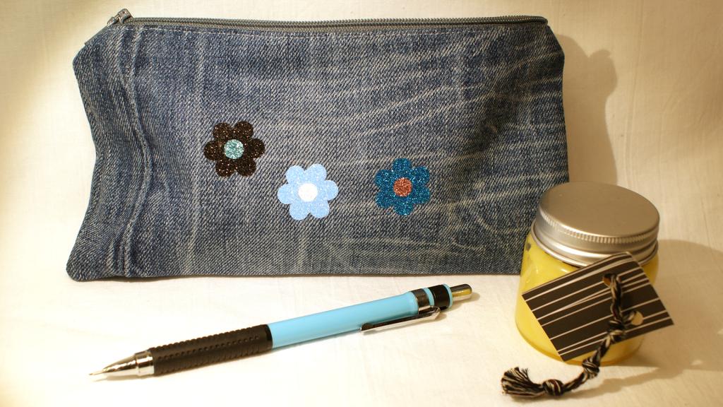 Mit Liebe handgemacht aus gertragenen Jeans ist dieses Täschchen mit blauem Reißverschluss und drei glitzernden Blümchen.