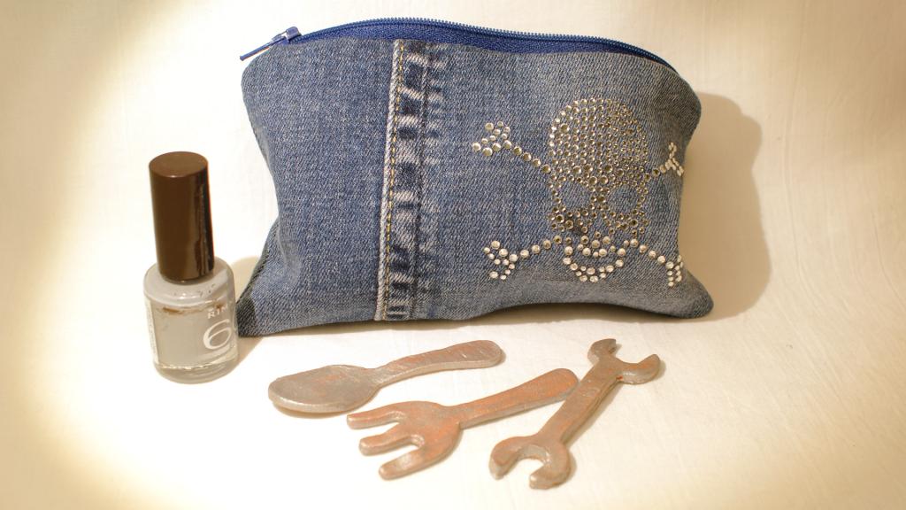 Kleines Täschchen aus getragenen Jeans mit blauem Reißverschluss und Totenkopf aus Strasssteinchen.