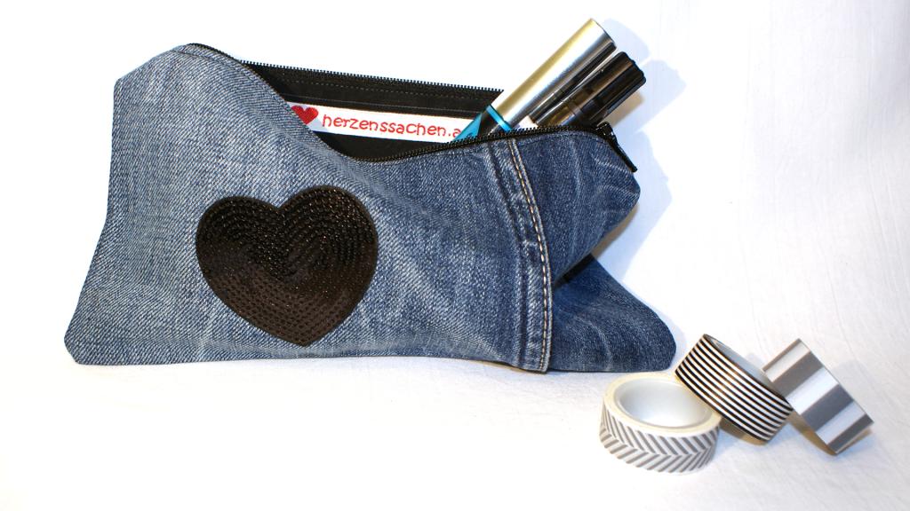 Jeanstascherl, mit schwarzem Reißverschluss, schwarz gemustertem Innenfutter und es ziert ein schwarzes Herz aus Pailletten.