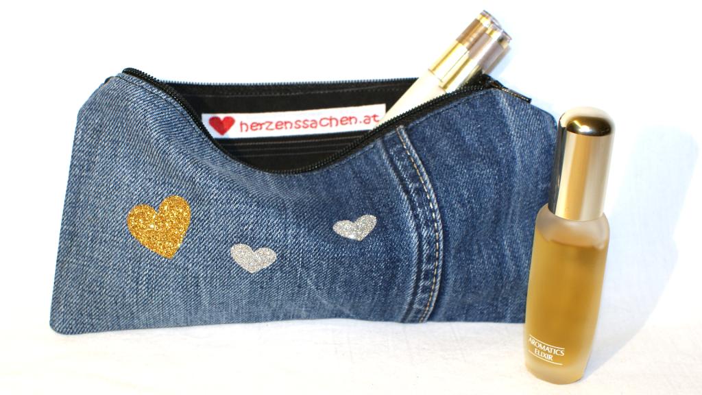 Selbstgenähtes Tascherl aus Jeans mit schwarzem Reißverschluss, schwarzem Innenfutter und süßen kleinen Gold- und Silberherzen auf der Vorderseite.